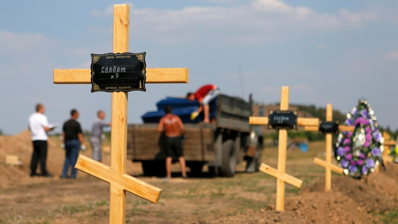 Employees unload a truck transporting coffins near graves of pro-Russian separatists at the Sixth Capital municipal graveyard on the edge of Donetsk